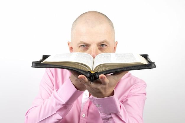 L'uomo barbuto in una camicia rosa guarda attraverso una bibbia aperta