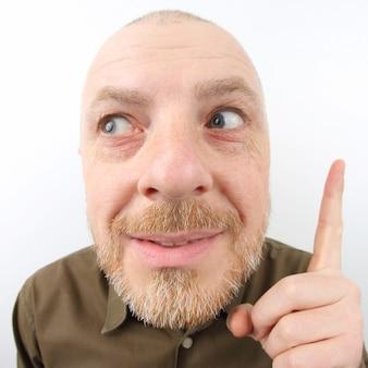 Uomo barbuto che punta il dito indice verso l'alto