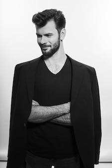 Uomo barbuto in posa in abito nero, guardando il lato, isolato