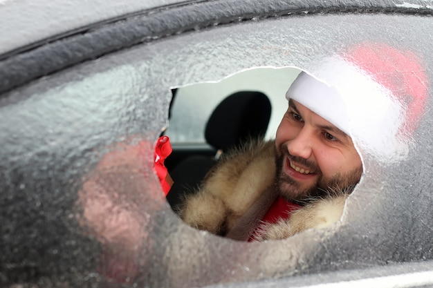 Uomo barbuto con un berretto rosso di babbo natale in un'auto con vetri rotti