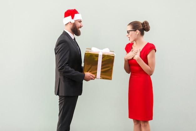 L'uomo barbuto in tazza rossa fa un regalo bella donna