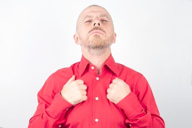 L'uomo barbuto in una camicia rossa sta con gli occhi chiusi