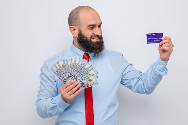 Uomo barbuto in cravatta rossa e camicia blu in possesso di contanti e carta di credito guardando la carta felice ed eccitato sorridente allegramente in piedi su sfondo bianco