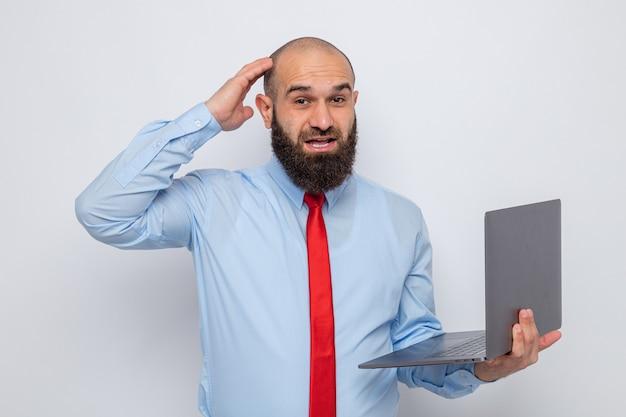 Uomo barbuto in cravatta rossa e camicia blu che tiene in mano un laptop che sembra confuso con la mano sulla testa