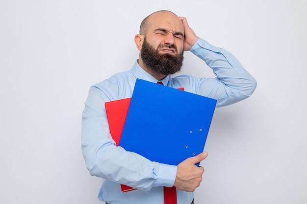 Uomo barbuto in cravatta rossa e camicia blu che tiene le cartelle dell'ufficio che sembra confuso e molto ansioso in piedi su sfondo bianco