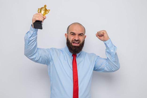Uomo barbuto in cravatta rossa e camicia blu che tiene il trofeo felice ed eccitato pugno serrato in piedi su sfondo bianco