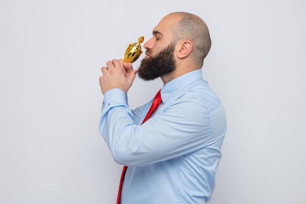 Uomo barbuto in cravatta rossa e camicia blu che bacia il suo trofeo felice e fiducioso in piedi su sfondo bianco