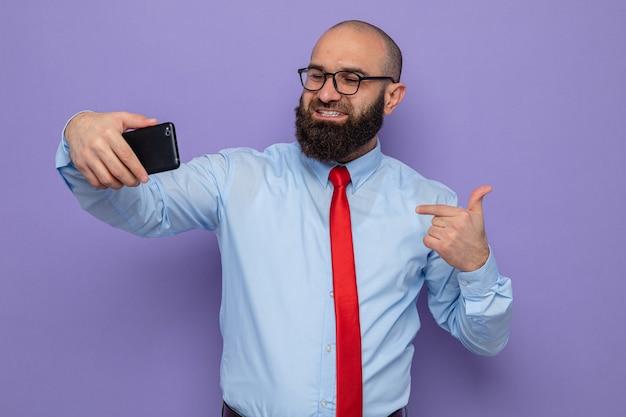 Uomo barbuto in cravatta rossa e camicia blu con gli occhiali che fa selfie usando lo smartphone, sorridendo allegramente indicando se stesso