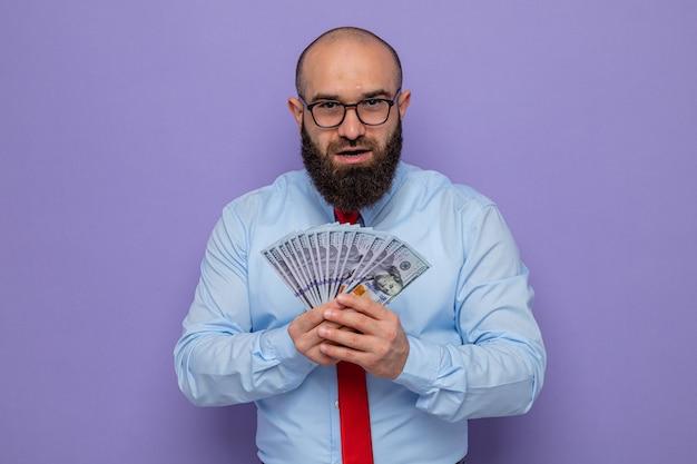 Uomo barbuto in cravatta rossa e camicia blu con gli occhiali in possesso di contanti che sembra sorridente allegramente felice ed eccitato