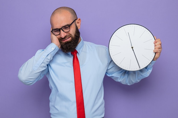 Uomo barbuto in cravatta rossa e camicia blu con gli occhiali con in mano l'orologio che sembra sorridente perplesso