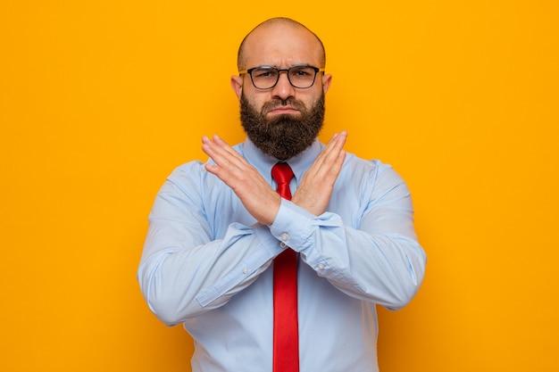 Uomo barbuto in cravatta rossa e camicia blu con gli occhiali che guarda la telecamera con una faccia seria che fa un gesto di arresto incrociando le mani in piedi su sfondo arancione