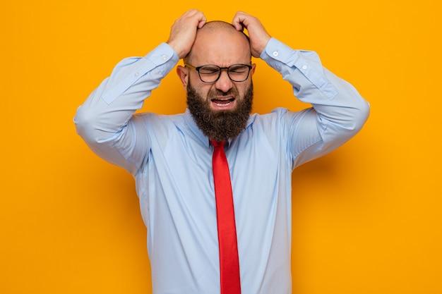 Uomo barbuto in cravatta rossa e camicia blu con gli occhiali che grida e urla pazzo pazzo e frustrato tenendosi per mano sulla testa in piedi su sfondo arancione