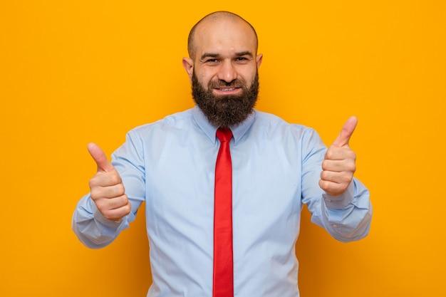 Uomo barbuto in cravatta rossa e camicia che guarda la telecamera felice e allegro sorridente che mostra ampiamente i pollici in su in piedi su sfondo arancione orange