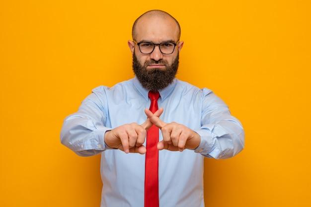 Uomo barbuto in cravatta rossa e camicia con gli occhiali che guarda la telecamera con una faccia seria che fa un gesto di arresto incrociando gli indici in piedi su sfondo arancione