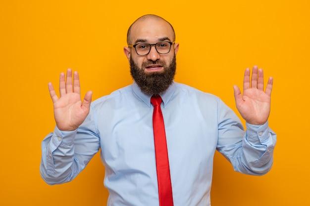Uomo barbuto in cravatta rossa e camicia con gli occhiali che guardano sorridenti mani con uvetta in segno di resa