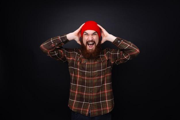 Uomo barbuto che grida mettendo le mani sulla sua testa, avendo un mal di testa su sfondo nero. pillole per mal di testa.
