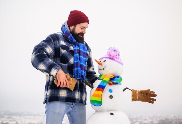 Uomo barbuto stringe la mano con pupazzo di neve babbo natale uomo con pupazzo di neve in inverno cappello inverno uomo in piedi
