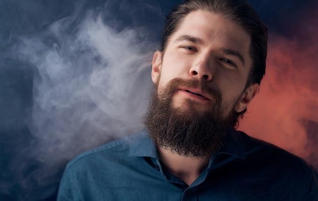 Uomo barbuto in camicia di fiducia in se stessi fumo primo piano