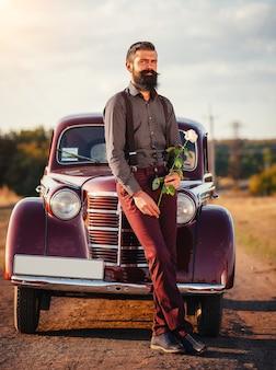 Uomo barbuto in camicia, pantaloni con bretelle tiene una rosa bianca in mano vicino a un'auto retrò marrone su una strada di campagna e guarda l'orologio
