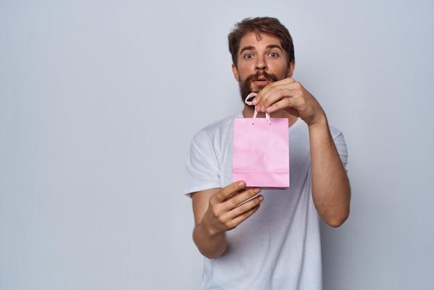 Uomo barbuto che mostra lo stile di vita del regalo pacchetto rosa