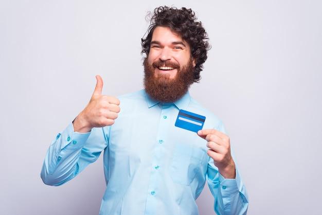 Uomo barbuto che mostra pollice in alto e carta di credito