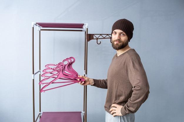 L'uomo barbuto mostra i ganci sullo sfondo del rack appendiabiti.