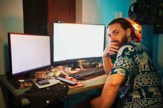 L'uomo barbuto si siede davanti al computer con 2 monitor e guarda la telecamera contro luci verde acqua e arancioni
