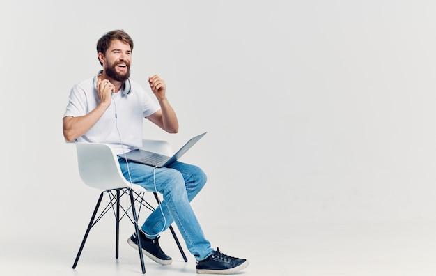 Uomo barbuto seduto su una sedia con un computer portatile sulla sua tecnologia in grembo