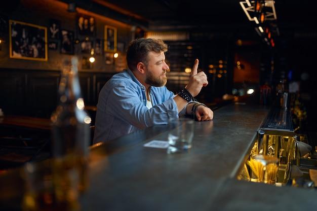 Uomo barbuto seduto al bancone del bar. una persona di sesso maschile arrabbiata in un pub, emozioni umane e attività ricreative, depressione, sollievo dallo stress