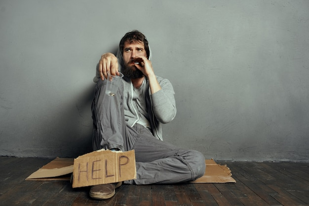 Uomo barbuto seduto sul pavimento implorando soldi problemi depressione