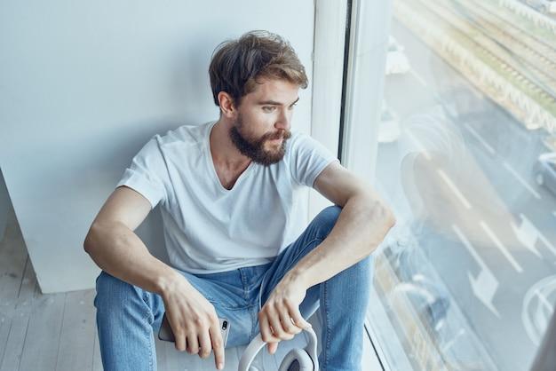 Uomo barbuto seduto vicino alla finestra in cuffia che ascolta musica sulla comunicazione in cuffia