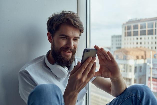 Uomo barbuto seduto vicino alla finestra in cuffia che ascolta musica in cuffia