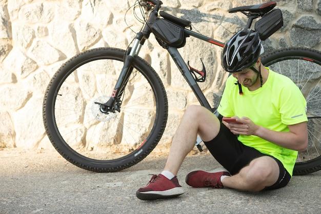Un uomo barbuto seduto con una bicicletta a noleggio per strada e comunica su uno smartphone