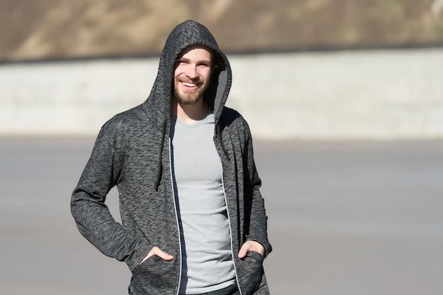 Sorriso dell'uomo barbuto in cappuccio su soleggiato all'aperto, moda. macho sorridenti in felpa, stile casual. moda uomo, stile, abbigliamento sportivo. stile di vita per l'uomo attivo e sano, lo sport.