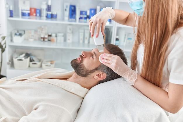 Uomo barbuto sorridente nel salone di bellezza professionale spa durante la procedura di pulizia del viso ad ultrasuoni.