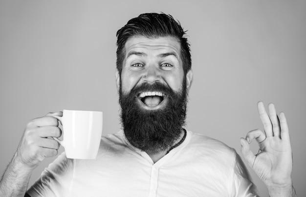 Uomo barbuto che sorride mostrando segno ok. buongiorno, uomo tè, ok. uomo sorridente dei pantaloni a vita bassa con la tazza di caffè fresco, uomo felice che mostra il segno giusto. l'uomo barbuto bello tiene una tazza di caffè, tè. bianco e nero.
