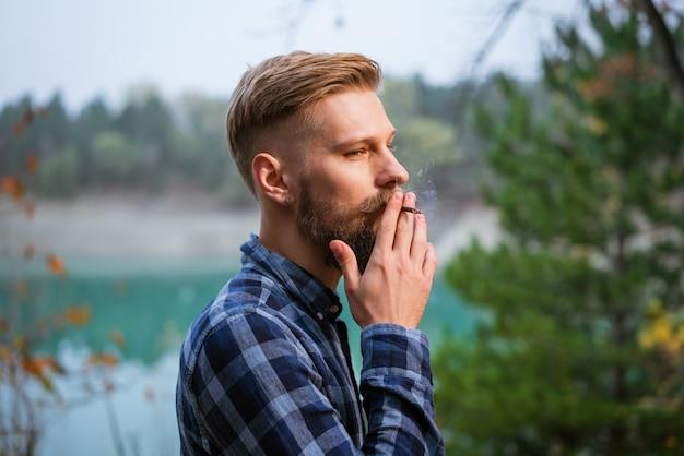L'uomo barbuto fuma un bell'uomo elegante in camicia a quadri con dipendenza da nicotina di sigaretta e cattivo