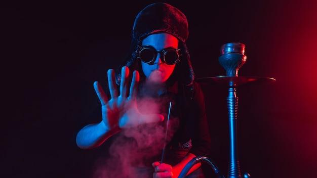 Uomo barbuto fuma uno shisha in un narghilè e soffia una nuvola di fumo su uno sfondo scuro con illuminazione al neon