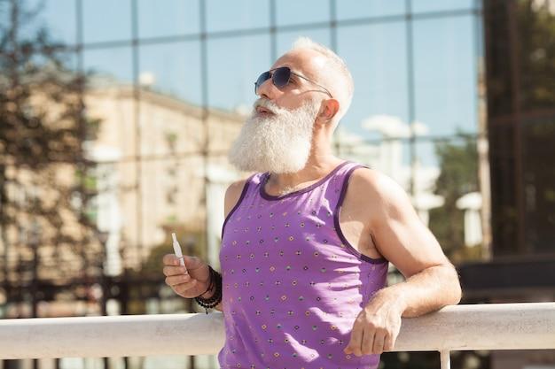 Uomo barbuto che fuma sigaretta elettronica. nuova tecnologia del fumo sano. iqos.