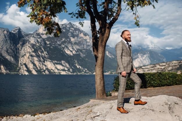 Un uomo barbuto in un rigoroso abito grigio a tre pezzi con una cravatta sullo sfondo delle alpi vicino al lago di garda, italia.