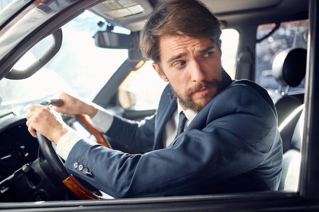 Uomo barbuto in giacca e cravatta in macchina un viaggio al lavoro ricco
