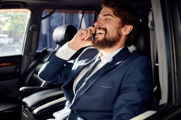 Uomo barbuto in giacca e cravatta in macchina un viaggio al servizio di lavoro. foto di alta qualità
