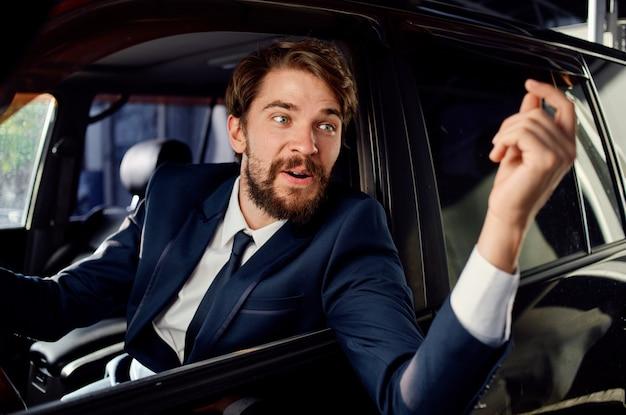Uomo barbuto in giacca e cravatta in macchina un viaggio al servizio di lavoro