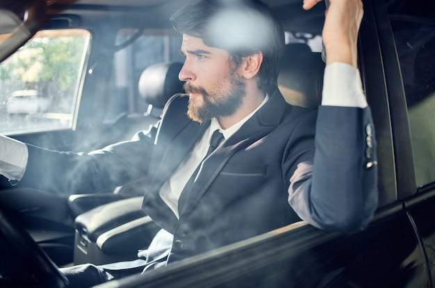 Uomo barbuto in giacca e cravatta in macchina un viaggio al lavoro successo