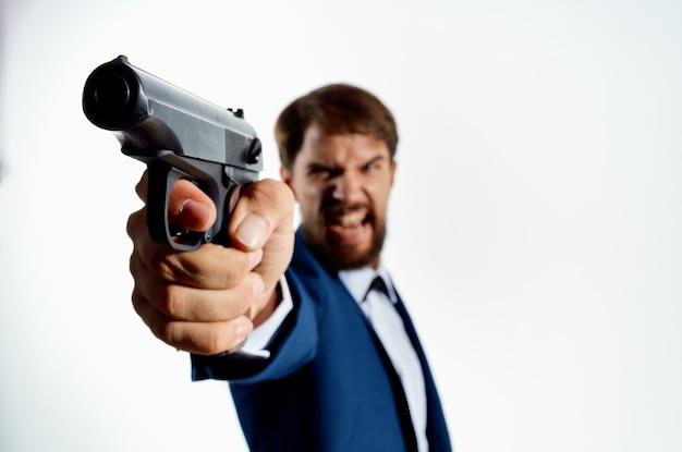 Uomo barbuto in tuta pistola close up assassino omicidio sfondo chiaro.