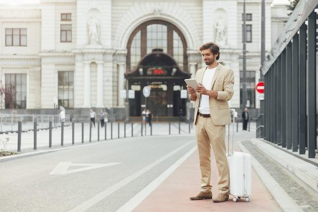 Uomo barbuto in vestito che tiene compressa digitale mentre si trovava vicino alla stazione ferroviaria con i bagagli