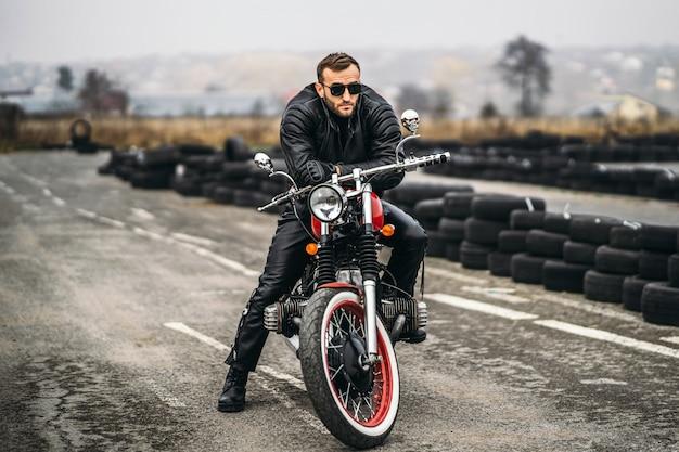 Uomo barbuto in occhiali da sole e giacca di pelle che esamina la macchina fotografica mentre era seduto su una moto sulla strada. dietro di lui c'è una fila di pneumatici
