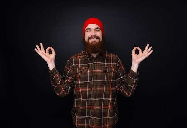 Uomo barbuto che respira profondamente meditando pacificamente sulla parete scura