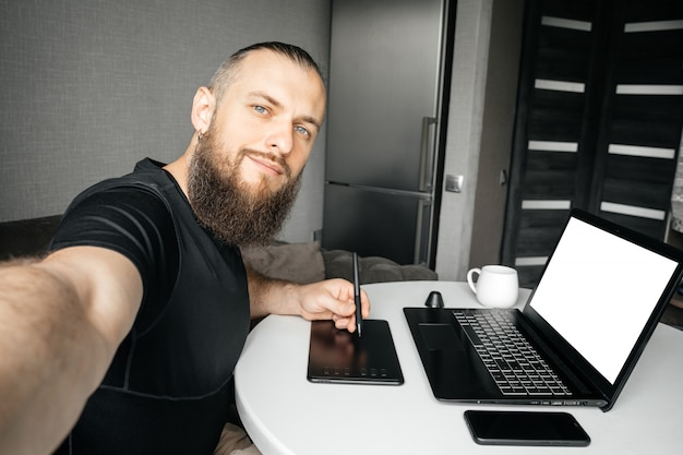 Uomo barbuto che prende i selfie nel suo posto di lavoro