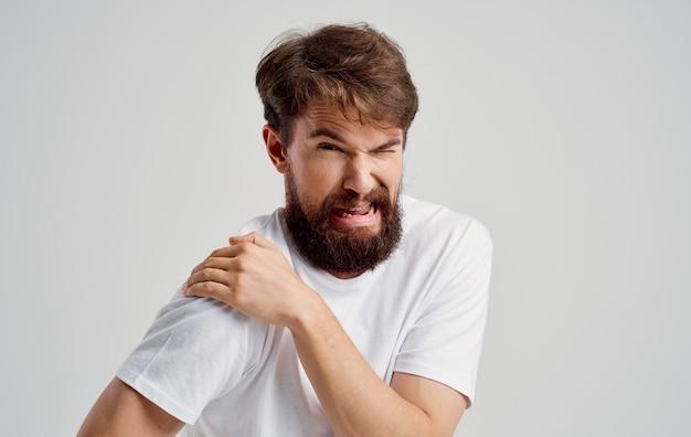 Uomo barbuto che tocca la spalla con intervento medico di dislocazione di dolore alla mano